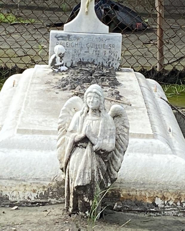 A cemetery in lower Lafitte, Louisiana, is covered with nearly a foot of marsh mud after Hurricane Ida struck the area on Aug. 29, 2021. Several of the caskets washed up and broke open during the storm. (Photo by Dianna Hunt/Indian Country Today)