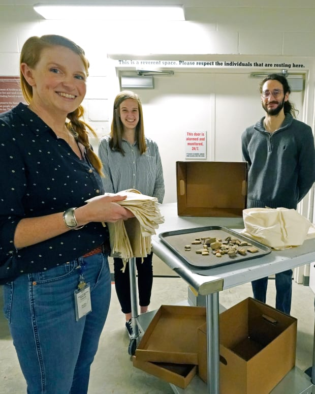 Meg Cook, director of the archeology collections for the Mississippi Department of Archives and History, left, joins team members, Jessica Walzer, archaeology collections manager, second from left, Robert Waren, NAGPRA (Native American Graves Protection and Repatriation Act) collections manager, second from right and Arianna Kitchens, archaeology collections manager by one of the work carts with unprovenienced prehistoric pottery and lithics that will be gathered into hand constructed muslin bags, Friday, March 19, 2021 outside the Two Museums' Archaeology Collections Storage room in Jackson, Miss. Several hundred Chickasaw ancestors and artifacts have been collected and will be repatriated to Native hands to be lain in their final resting place at an undisclosed location in the state. (AP Photo/Rogelio V. Solis)