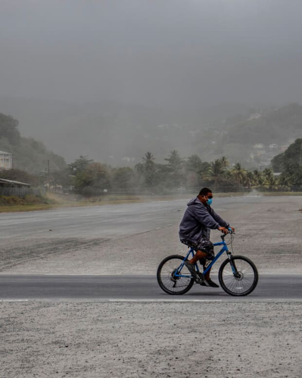 A man rides his bicycle past fields covered with volcanic ash a day after the La Soufriere volcano erupted, in Kingstown, on the eastern Caribbean island of St. Vincent, Saturday, April 10, 2021. (AP Photo/Lucanus Ollivierre)