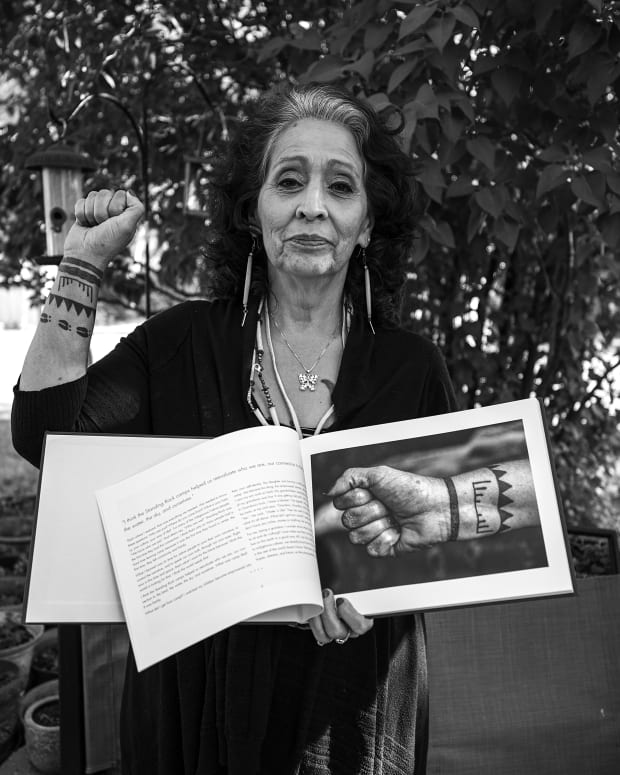 "LaDonna Tamakawastewin Allard in June 2019 at her home holding the photography book, ""Standing for Unity: The Standing Rock Movement,"" by Eugene Tapahe. Tapahe presented her with the book, she was one of the contributors. (Photo by Eugene Tapahe, Tapahe Photography)"