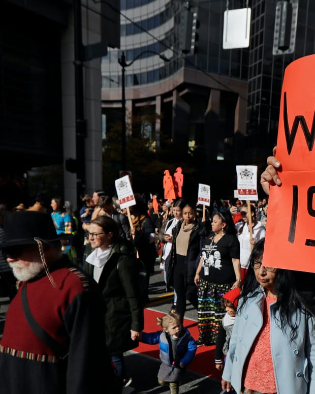 "Dennis Willard, of Bellevue, Wash., carries a sign that reads ""Where Is She"" as he marches in support of missing and murdered indigenous women during a rally to mark Indigenous Peoples' Day in downtown Seattle, Monday, Oct. 14, 2019. The observance of the day was made official by the Seattle City Council in 2014, and it takes place annually on the federal holiday of Columbus Day. (AP Photo/Ted S. Warren)"