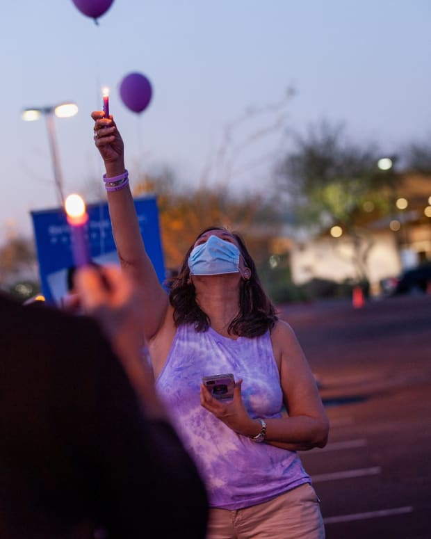 Theresa Guerrero, of Tucson, raises a candle in memory of those lost to drug overdoses during an event in Gilbert, Ariz., on March 31, 2021. Her son died of a fentanyl overdose last May, and she says his struggles with drugs were exacerbated by isolation brought on by the pandemic. (Photo by Alberto Mariani/Cronkite News)