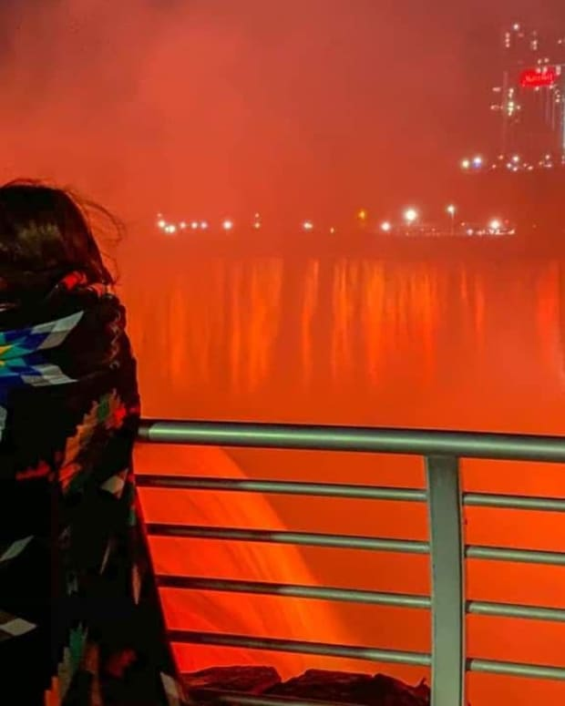 Kyrie Buffalo, 13, of the Seneca Nation (Turtle Clan), peers at the Canadian Horseshoe Falls while wrapped in a blanket on May 31, 2021. All three waterfalls, totaling about 800,000 gallons of water per second, were illuminated orange on Memorial Day in honor of the 215 children found in a mass grave at the site of the former Kamloops Indian Residential School in British Columbia. (Photo by Kateri Capton-Serpas via Ken Cosentino)