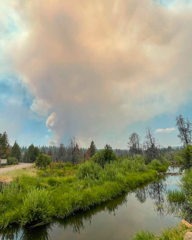 In this photo provided by the Bootleg Fire Incident Command, the Bootleg Fire burns in the background behind the Sycan Marsh in southern Oregon on Saturday, July 17, 2021. The destructive Bootleg Fire, one of the largest in modern Oregon history, has already burned more than 476 square miles (1,210 square kilometers), an area about the size of Los Angeles. (Bootleg Fire Incident Command via AP)