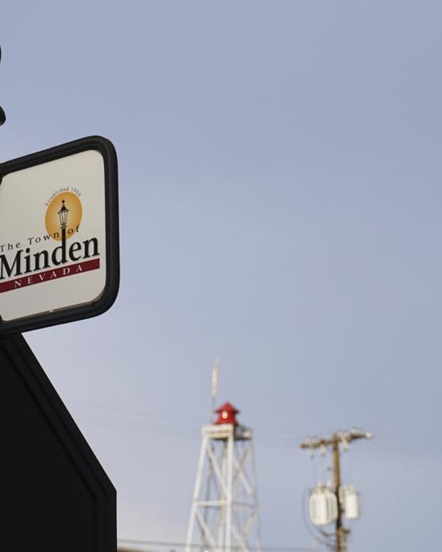 """This June 30, 2021 photo shows a sign for the town of Minden, Nev. Efforts to silence the century-old siren, seen in the background, that blares every night at 6 p.m. are sparking debates over how to confront the region's history of racism and violence. The Washoe Tribe of Nevada and California associates the siren with a historic """"sundown ordinance"""" that once made it illegal for them to be in Minden and neighboring Gardnerville after nightfall. Residents of the mostly white town defend it as a tradition that marks time and honors first responders. After state lawmakers banned the siren, the Washoe Tribe's chairman and Minden town manager agreed to move the siren to 5 p.m. but the compromise left many tribal members unsatisfied and awaits discussion at the tribal council. (AP Photo/Sam Metz"""