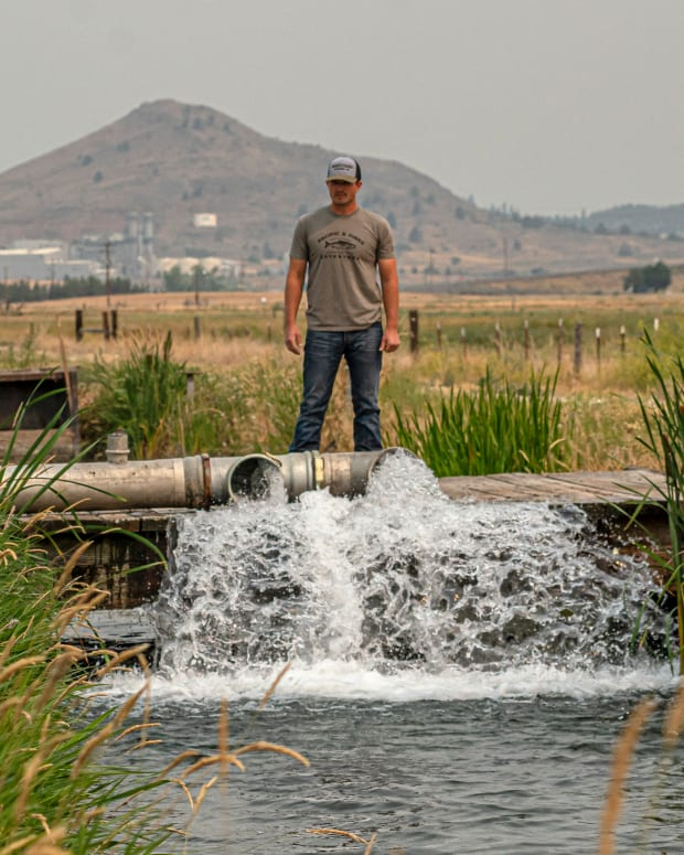Justin Grant watches water flow from his agricultural well, Saturday, July 24, 2021, in Klamath Falls, Ore. Dozens of domestic wells have gone dry in an area near the Oregon-California border where the American West's worsening drought has taken a particularly dramatic toll. (AP Photo/Nathan Howard)