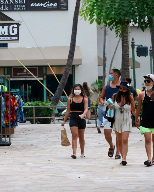 FILE - In this Aug. 24, 2021 file photo people walk past Waikiki restaurants and shops in Honolulu. The mayor of Honolulu says starting Sept. 13 the city will require patrons of restaurants, bars, museums, theaters and other establishments to show proof of vaccination or a recent negative test for COVID-19. (AP Photo/Caleb Jones, File)