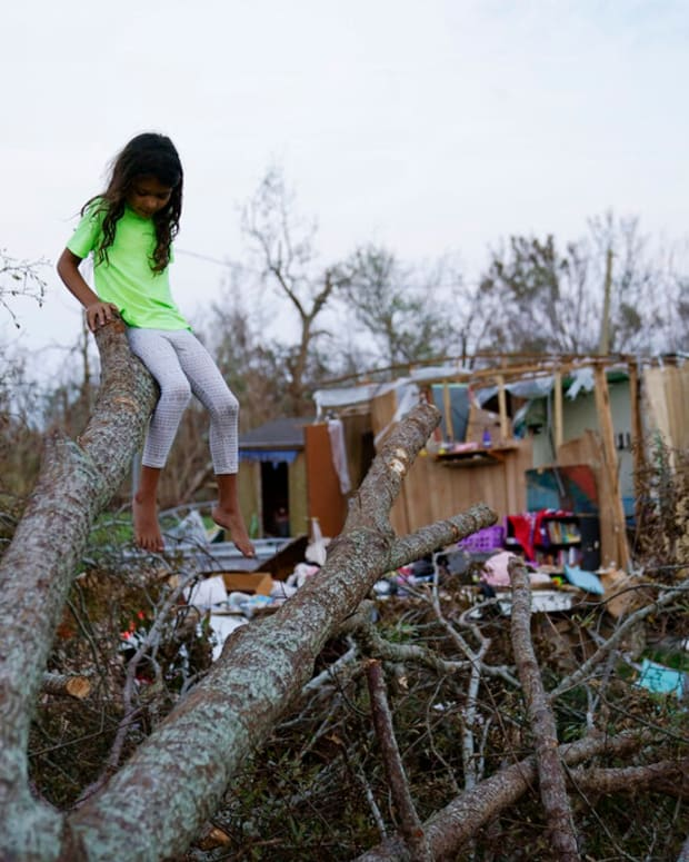 In this Sept. 4, 2021 file photo, six-year-old Mary-Louise Lacobon sits on a fallen tree beside the remnants of her family's home destroyed by Hurricane Ida, in Dulac, La. Louisiana students, who were back in class after a year and a half of COVID-19 disruptions kept many of them at home, are now missing school again after Hurricane Ida. A quarter-million public school students statewide have no school to report to, though top educators are promising a return is, at most, weeks away, not months. (AP Photo/John Locher, File)