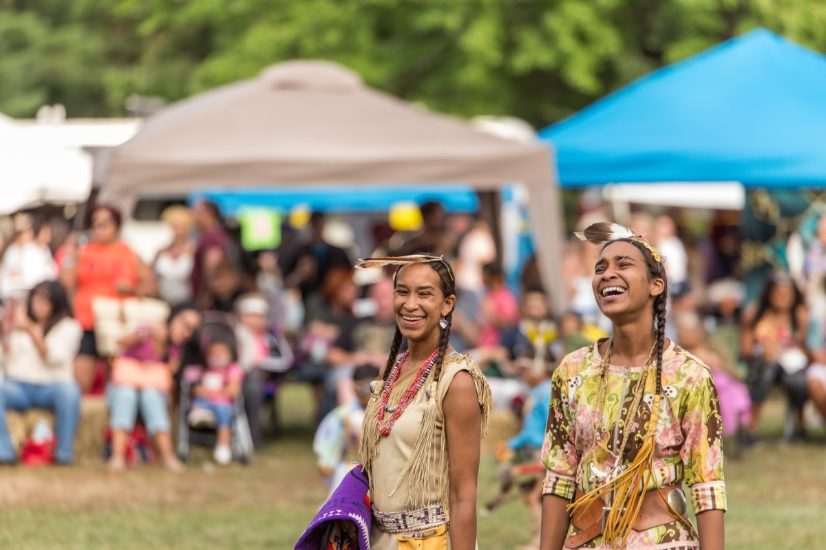 Dancers share a laugh during the intertribal dance portion. Photo: Alex Hamer