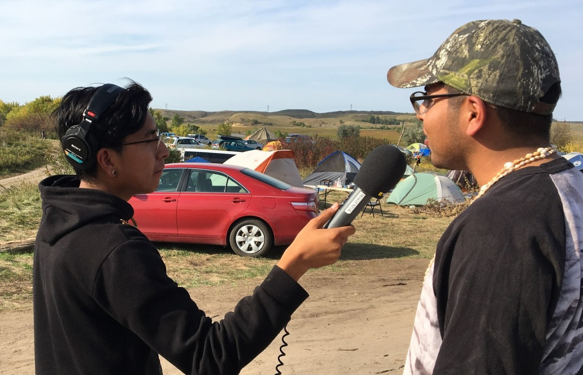 """DJ Skeg chu (Beautiful one, real name Damien Carlos, from the community of Sil Najka, Saddle Hang, Tohono O'odham Nation) on remote assignment in Standing Rock Sioux Nation interviewing a """"Water Protector."""" - Courtesy KOHN Radio / Multimedia"""