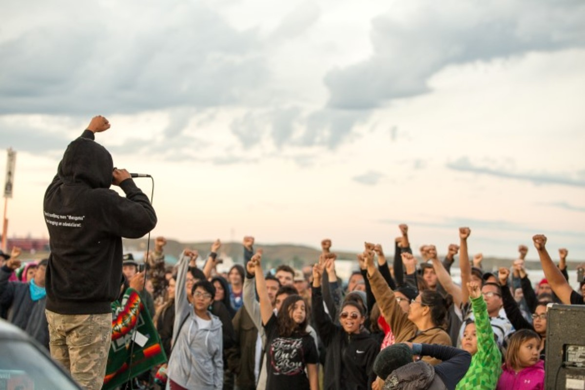Quese IMC (Indigenous MC), aka Marcus Frejo Little Eagle leading the youth with fists in the air. He was one of those arrested on the front lines at Standing Rock. Photo-Alex Hamer