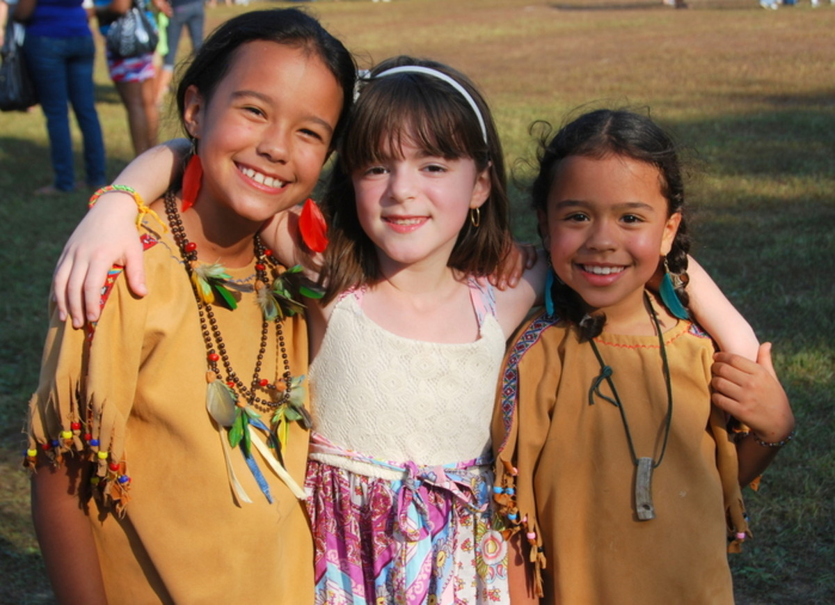 Three young women share big smiles at a pow wow. Photo Vincent Schilling International Women's Day.