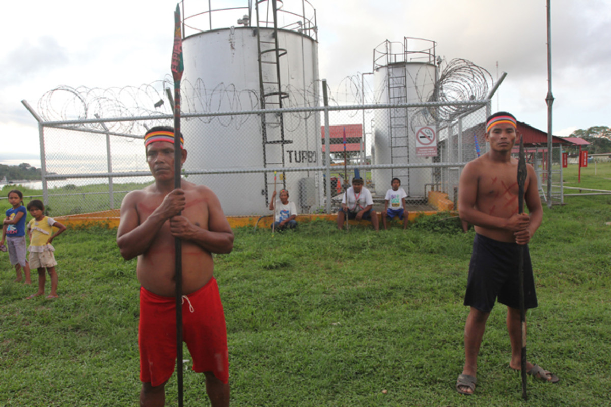 Indigenous Protestors Flanked by tanks at an Oil station in Peru