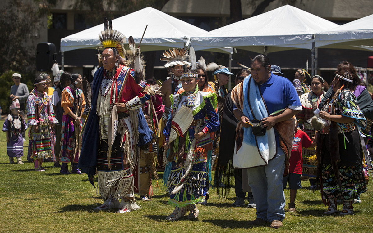 UCSD Pow Wow 2017: A small procession moves through the powwow circle during a special for the head girl Olivia Sheridan, center.