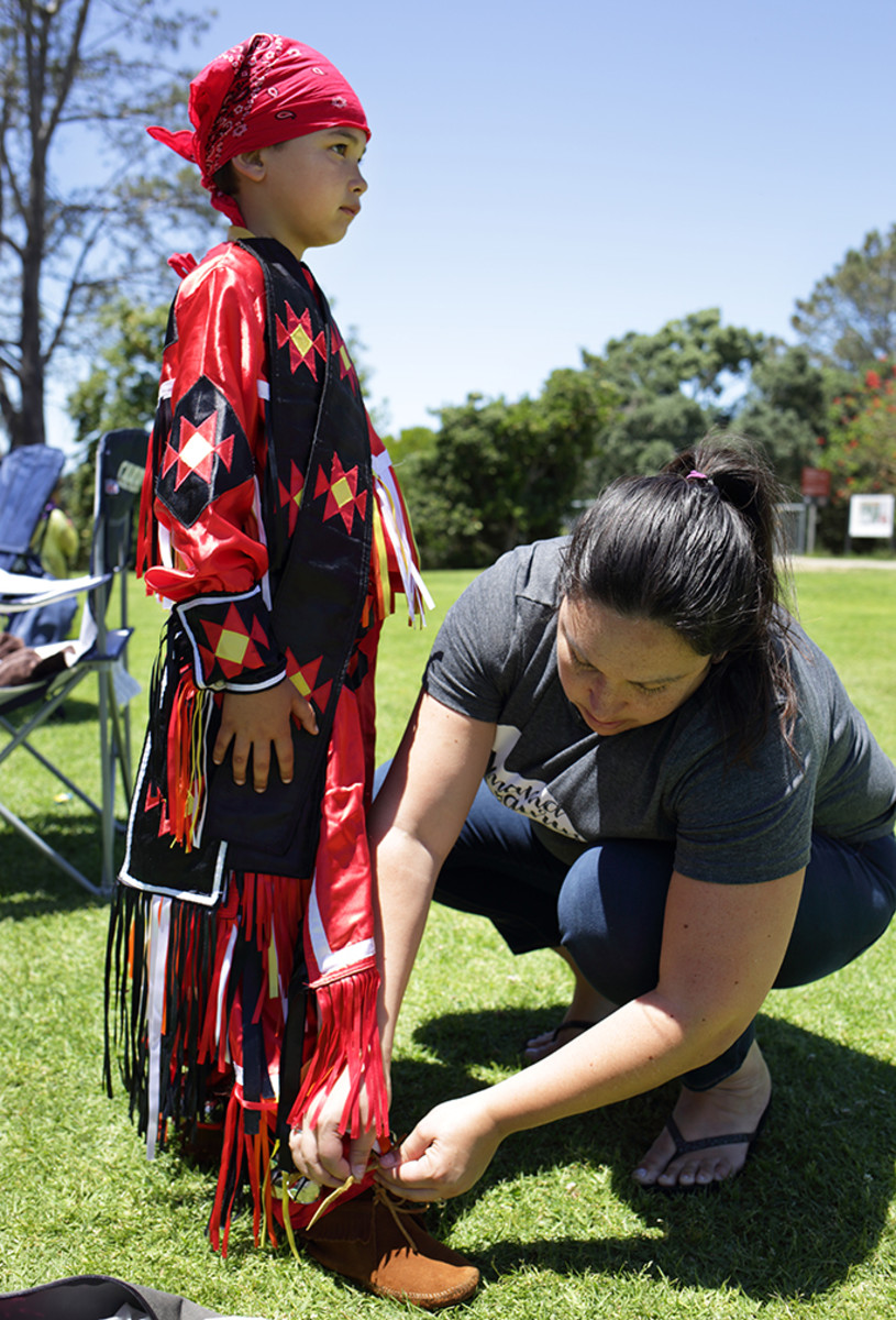 UCSD Pow Wow 2017: Grass dancer Daniel Camacho, 8, Apache/Pascua Yaqui, gets help with his moccasins from his mother Melanie before an intertribal during the 7th Annual UCSD Powwow, on Saturday afternoon, May 20, 2017, in San Diego, Calif.