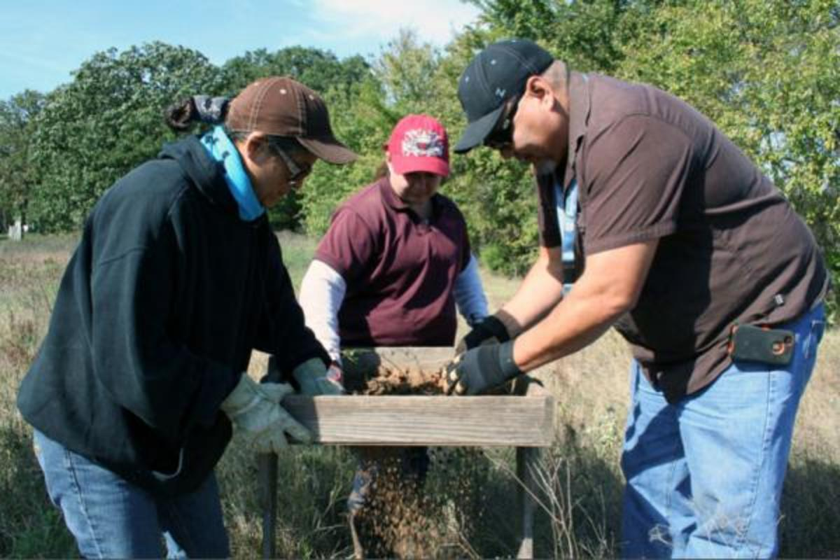 Cynthia Highfield, Ambrie Johnson and Joey Seeley, environmental specialists for the Chickasaw Nation, carefully sift through a soil sample collected from a shovel test pit.