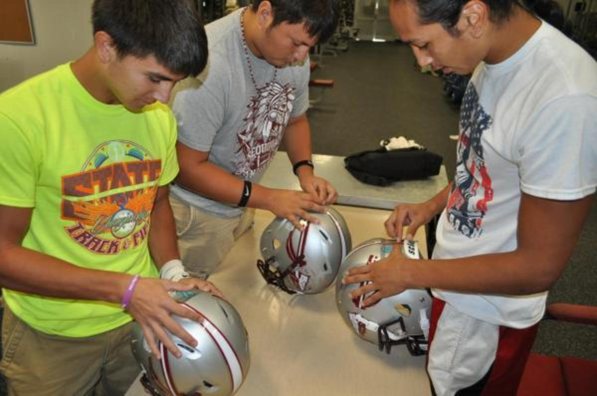 """Left to right: Sequoyah High School senior football players Cody Hooper, Elijah Tucker and Nick Kingfisher apply blue ribbons for prostate cancer awareness to their helmets for Friday night's """"Man Up Game"""" against Beggs."""
