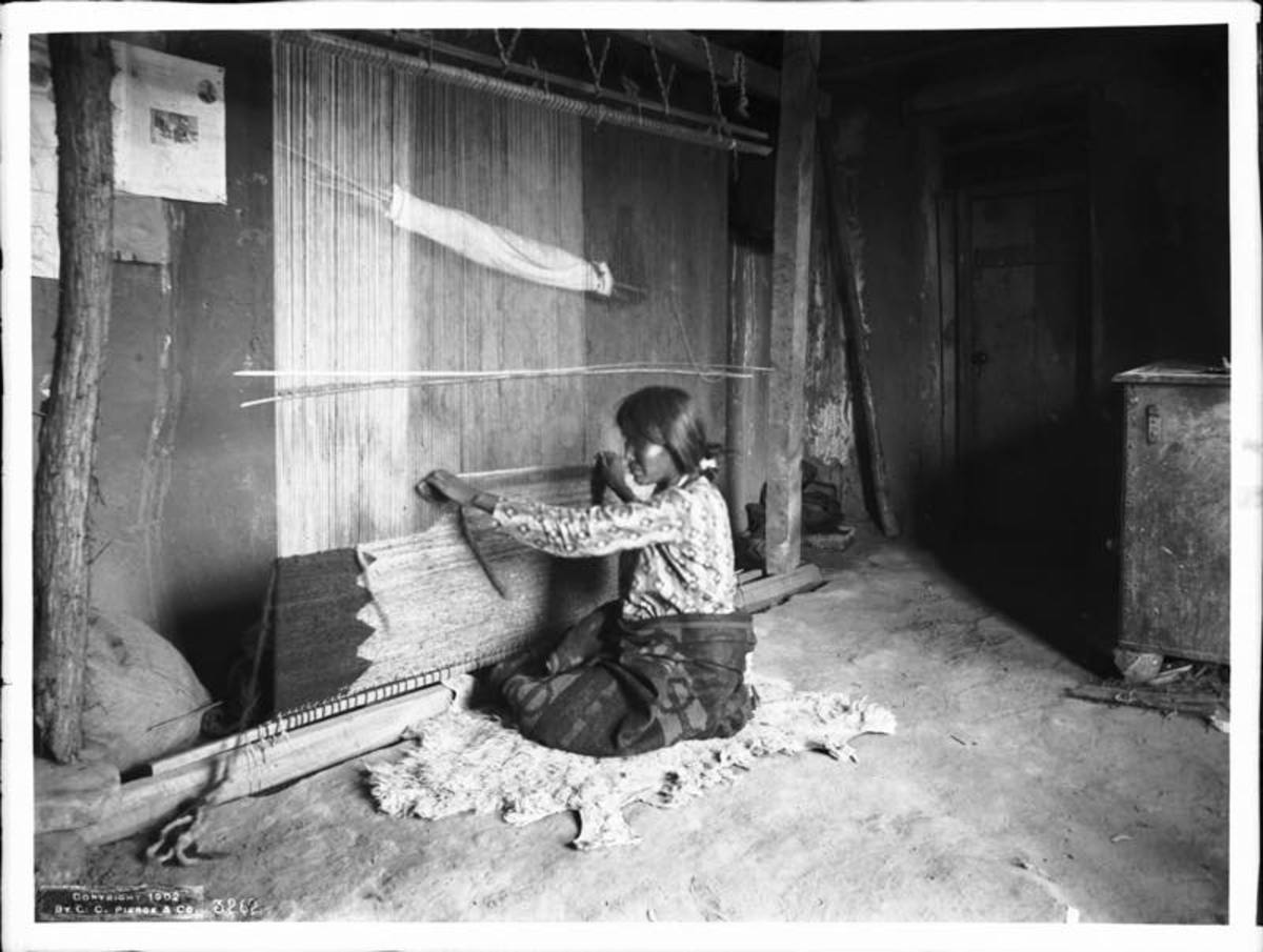 A Navajo woman weaves a blanket around 1901.