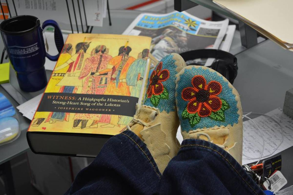 "Monica Braine ""Rocs her Mocs"" amidst a book by a Native author."