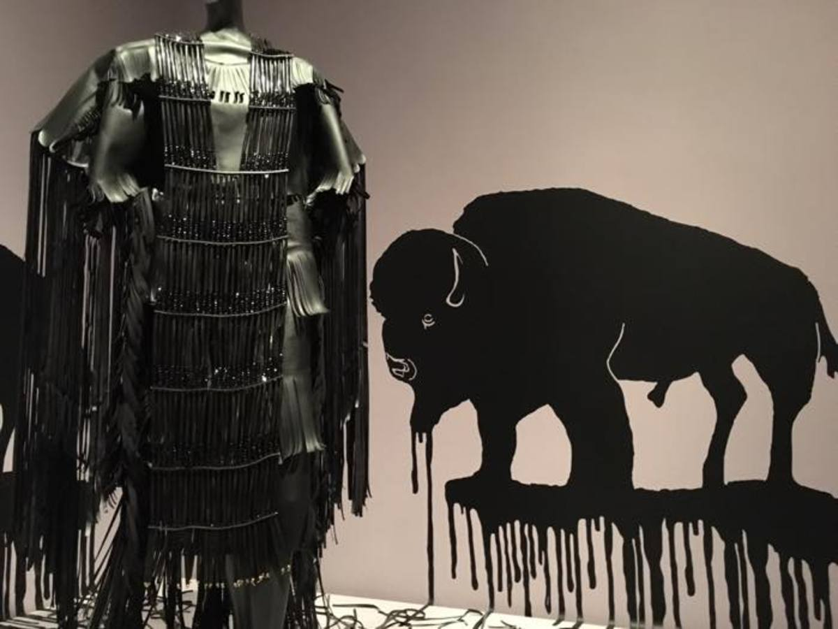 Apsáalooke Wendy Red Star's dress stands  in front of buffalo silhouettes designed by Terrance Houle (Blood). The collaboration draws attention to the depletion of natural resources on Native lands.