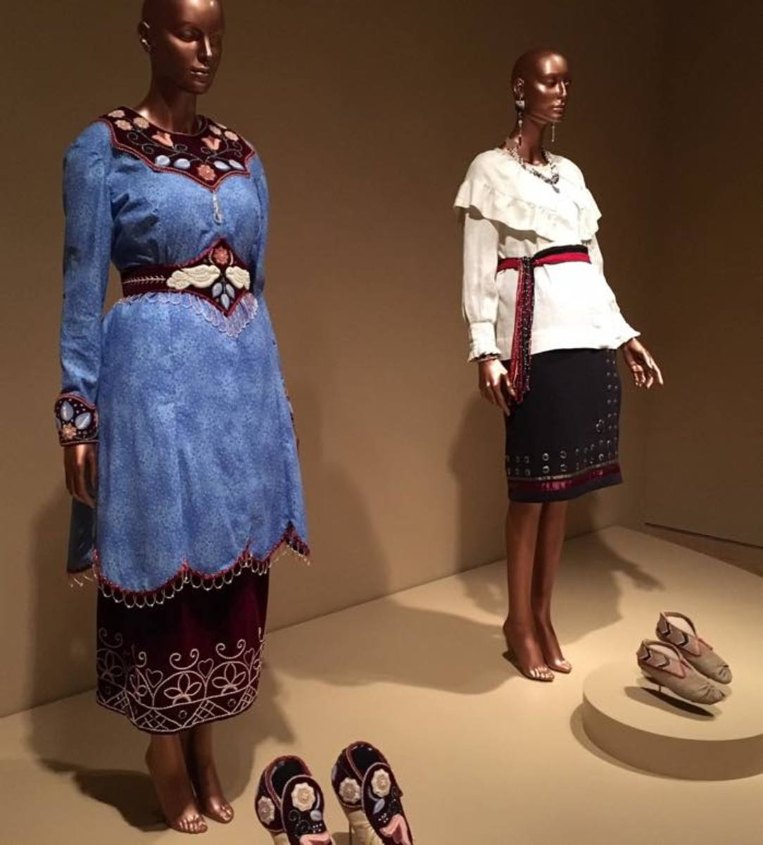 """The ensemble on the left, titled Emma, by Niio Perkins (Akwesasne Mohawk) shows the endless possibility of beadwork, which is rooted in her Native heritage. The ensemble on the right is by Elizabeth James-Perry (Aquinnah Wampanoag). """"The colors, textures, the creative rhythm of someone… weaving and threading and beading together a certain pattern; it's like telling a story,"""" James-Perry said. """"Being part of that storytelling process is central to my identity as a Wampanoag woman."""""""