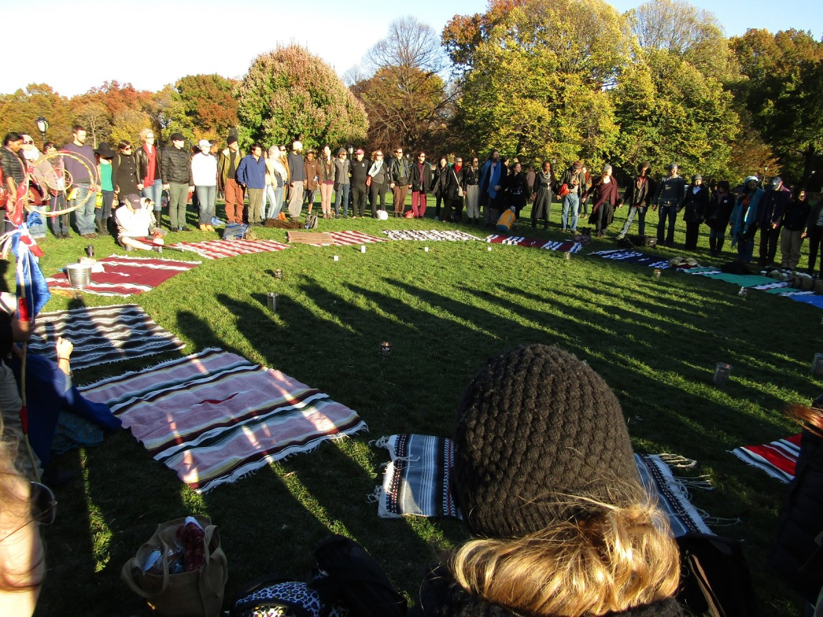 After laying blankets in a sacred circle, tribal members and friends joining hands in prayer - Photo Cliff Matias