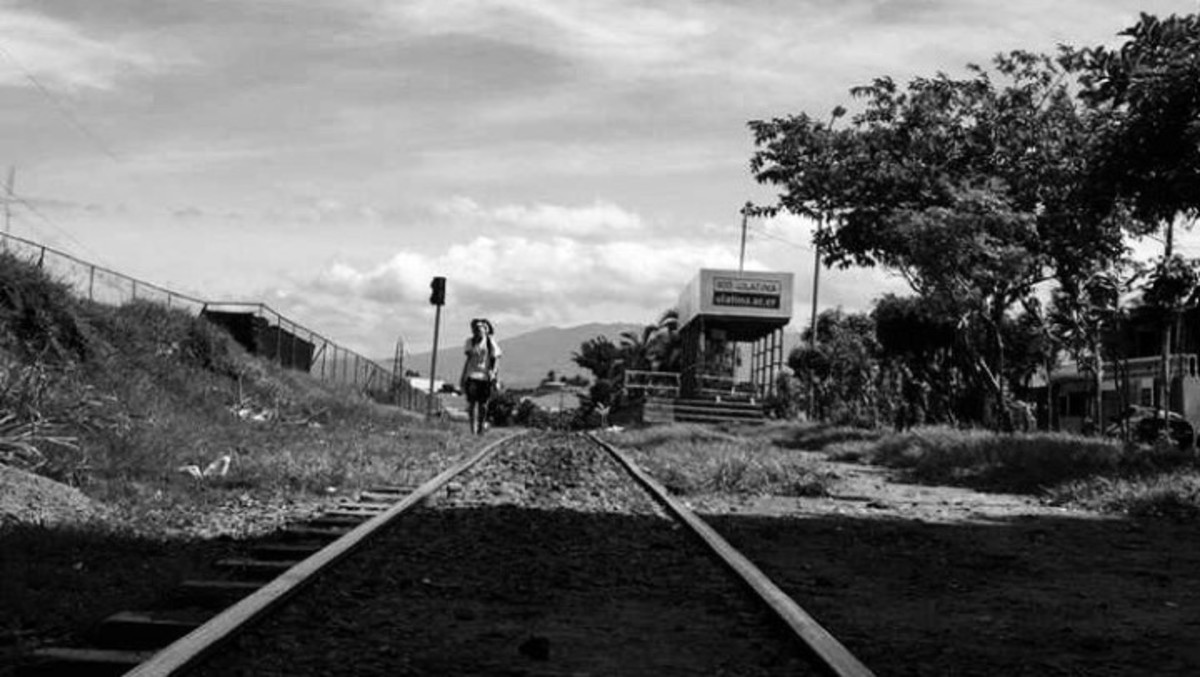 Rene Reyes following the train tracks on his way to school in Heredia, Costa Rica. Photo - Christian Gomez