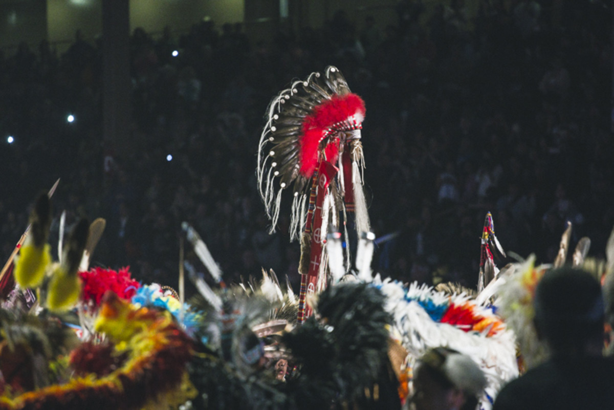 Flag bearers and veterans carry a headdress during the honor songs at the Gathering of Nations pow wow. Thosh Collins