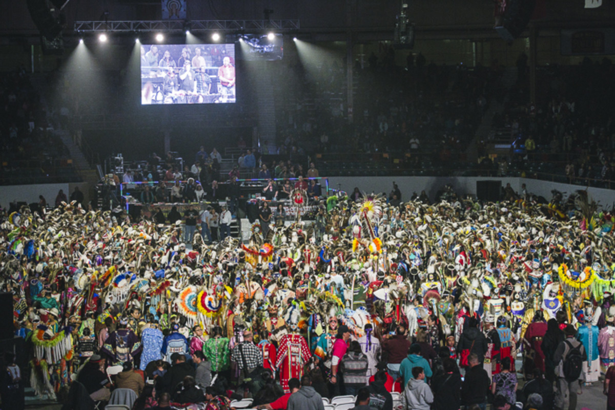 Hundreds of dancers and drummers look toward the announcer's booth while an honor song is sung for veterans after the Gathering of Nations' Grand Entry. Thosh Collins