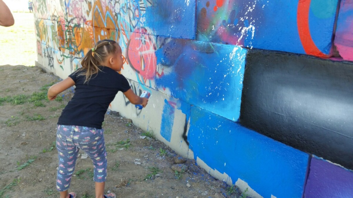 A young Native girl takes Martinez's teachings to heart and uses the wall as her canvas in Eagle Butte. Scape Martinez will lead a four-day graffiti art camp starting May 30th benefiting Native Youth in Eagle Butte.