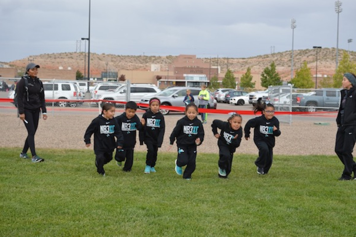Left to right: Ethan Gutierrez, Quinton Begay, Kyrie Lujan, Edwina Paisano, Julyssa Montoya, and Mikayla Sanchez practice their sprints during warm-up for NB3XC's second meet of the season held at Rio Rancho High School on October 8, 2016. Coach Kalei Yepa (left) and Coach Kassandra McCook (right) lead the warm-up and encourage the kids.
