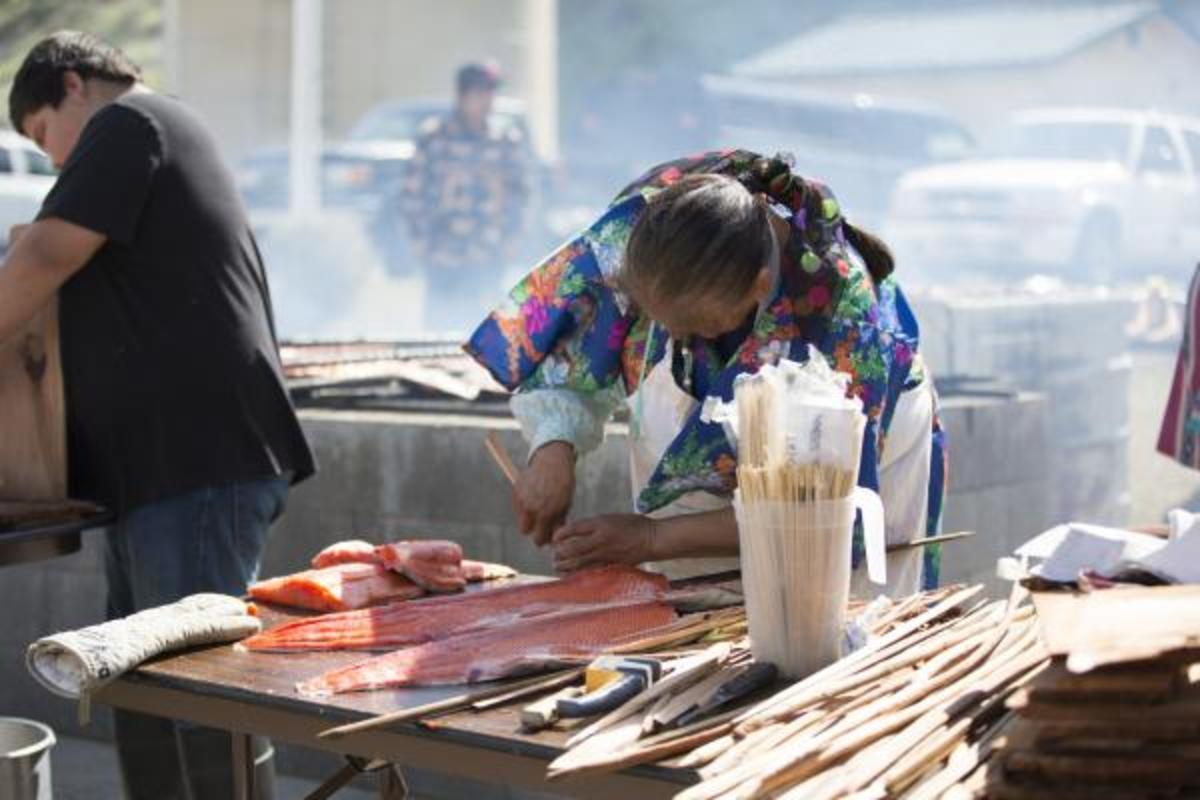 An elder prepares salmon, a traditional dish for many Indian nations.