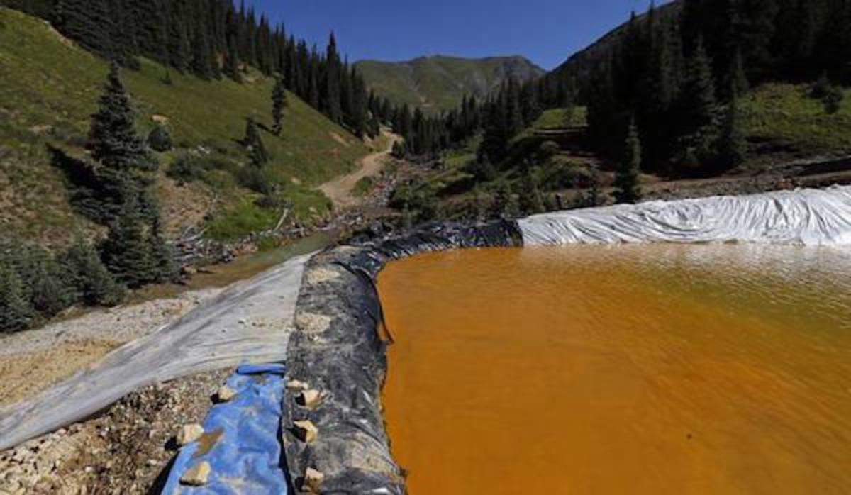 Water flows through a series of sediment retention ponds built to reduce heavy metal and chemical contaminants from the Gold King Mine wastewater accident, in the spillway about 1/4 mile downstream from the mine, outside Silverton, Colo., Friday, Aug. 14, 2015.