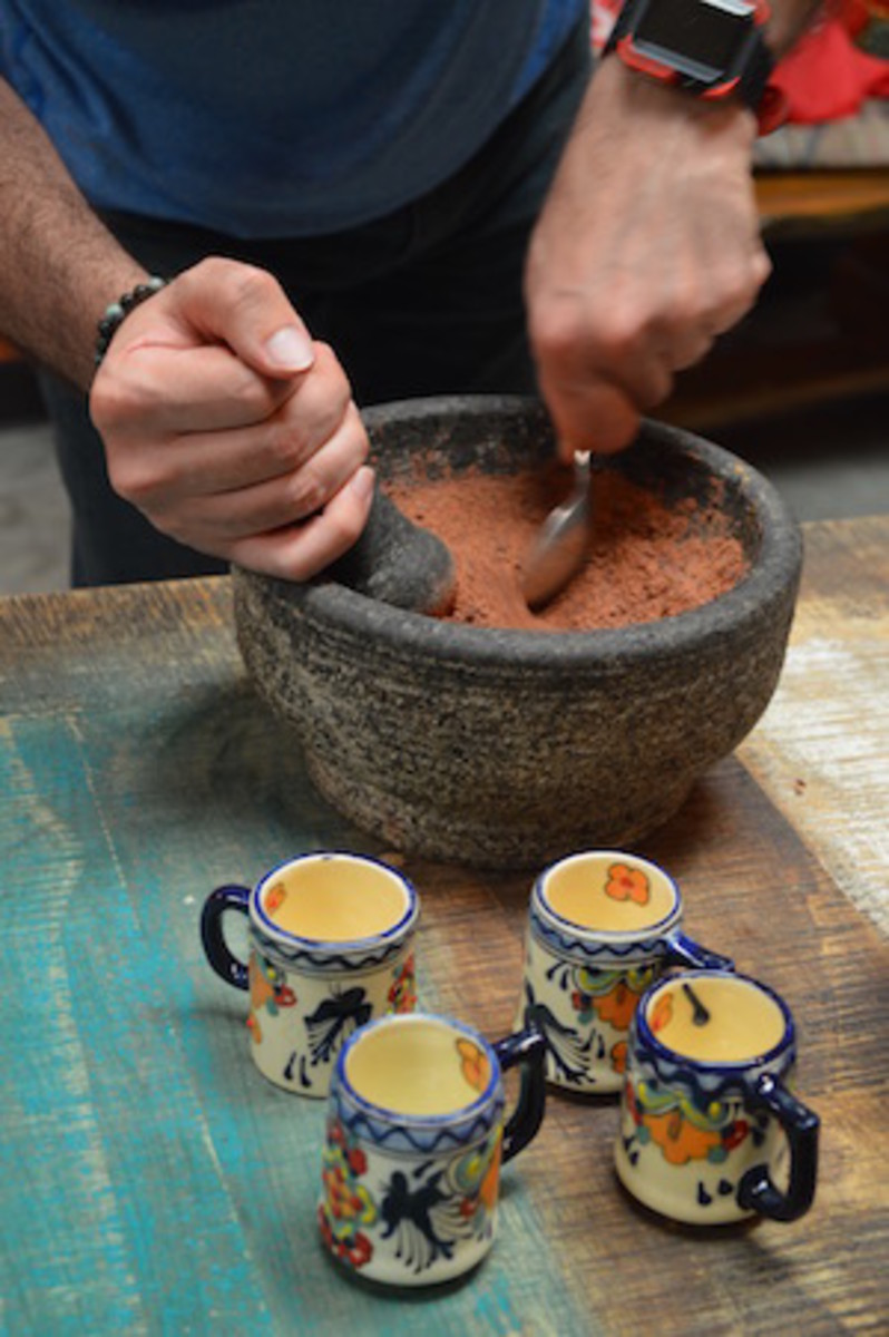 Vahid Behravan uses Mesoamerican traditional mortar and pestle to grind spices into the cocoa.