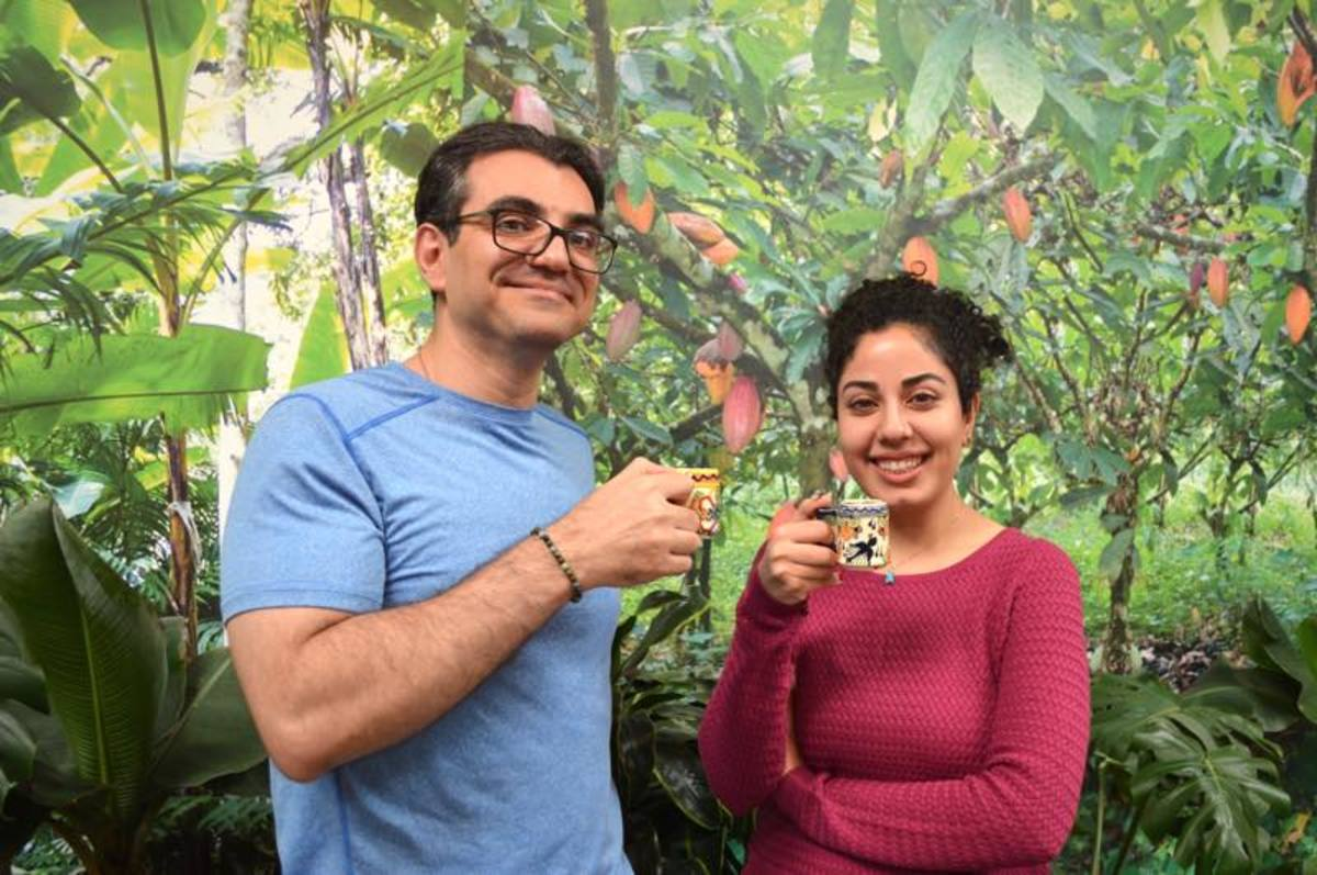 Vahid Behravan and Shirin Zoufan sip some of their chocolate creations in front of a photo mural of a cocoa forest.