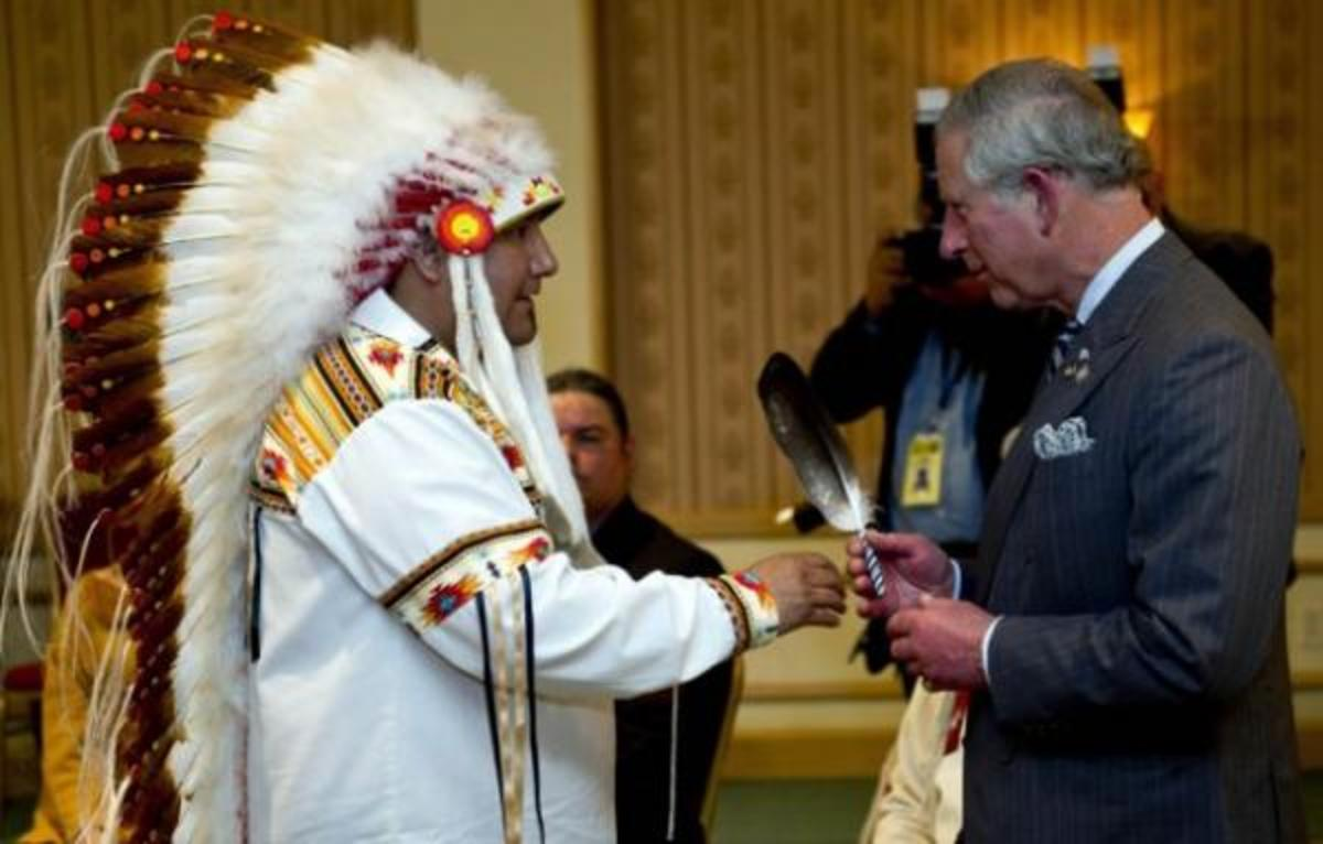 Grand Chief David Harper of Manitoba Keewatinowi Okimakanak presents Prince Charles with an eagle feather during his tour with wife Camilla, Duchess of Cornwall, commemorating Queen Elizabeths Diamond Jubilee.