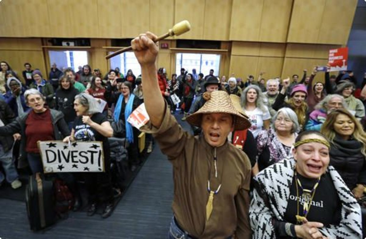 Pictured: Olivia One Feather, right, of the Standing Rock Sioux tribe, and Paul Cheoketen, of the Wagner Saanich First Nations, at the Feb. 7, 2017 meeting when the Seattle City Council voted to sever ties with Wells Fargo. (AP Photo/Elaine Thompson)