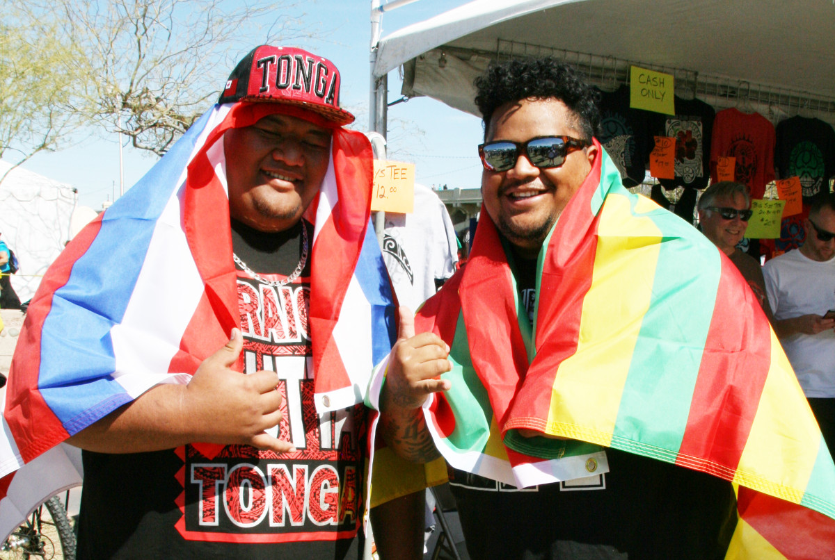 Senio Samisoni and Isaac Agiga show their Pacific Islander spirit with colors and flags. by Debra Krol