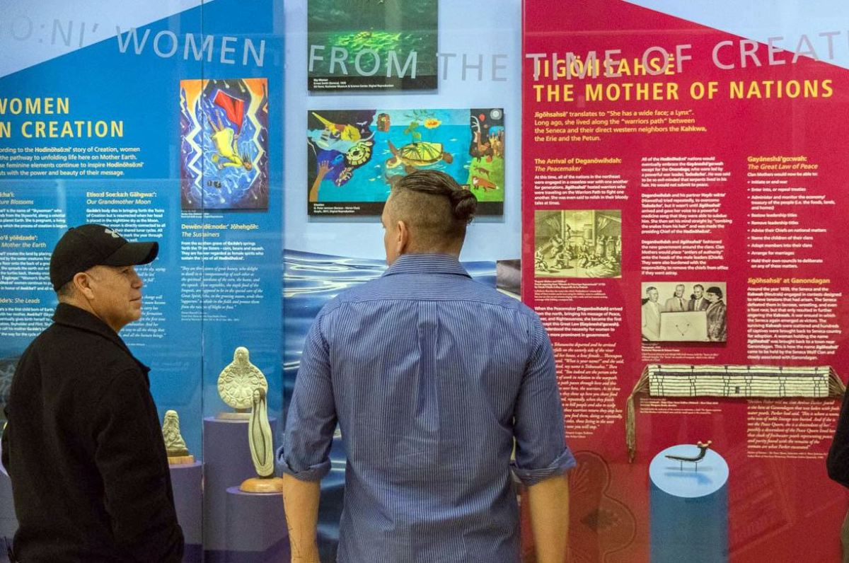 Two men observe with respect at the Women in Creation and Mother of Nations exhibit.