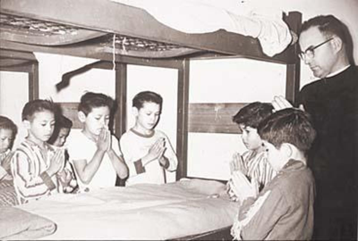 Boys pray before bedtime with Father Keyes at St. Mary's Mission boarding school in Omak, Washington. (Photo courtesy of the Northwest Museum of Arts and Culture)