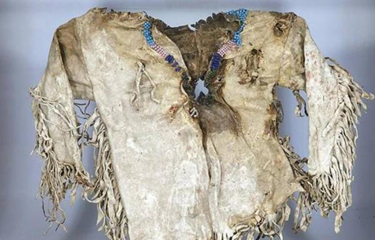 Lot 22 - 'Northern Plains Indian Child's Tunic, early 19th century fringed and with beaded collar, showing signs of central bullet trauma.'