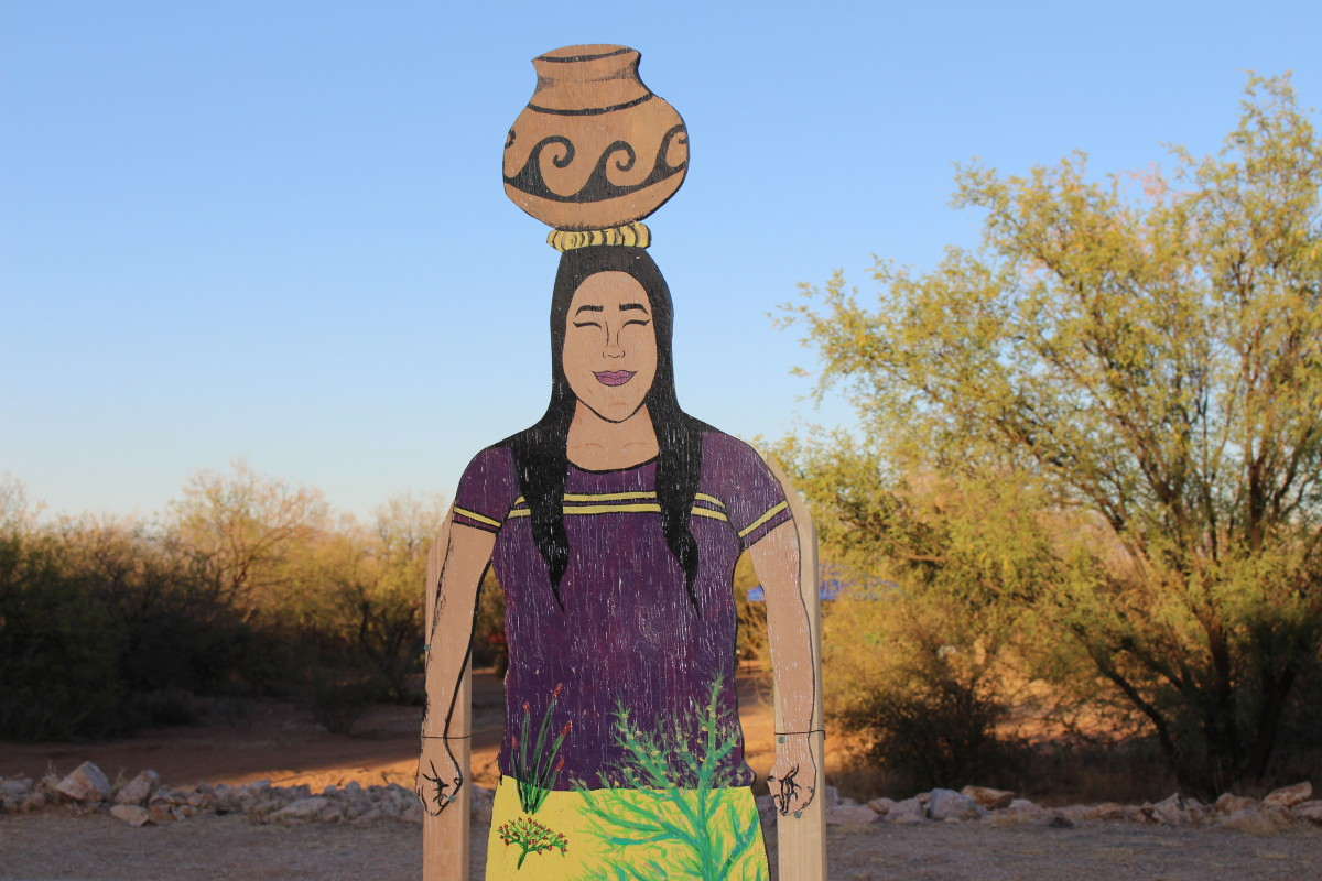 An art panel from the O'odham Women's Community Art Project. This panel depicts an O'odham woman in traditional dress carrying a pot on her head, historically a common method of transporting materials.