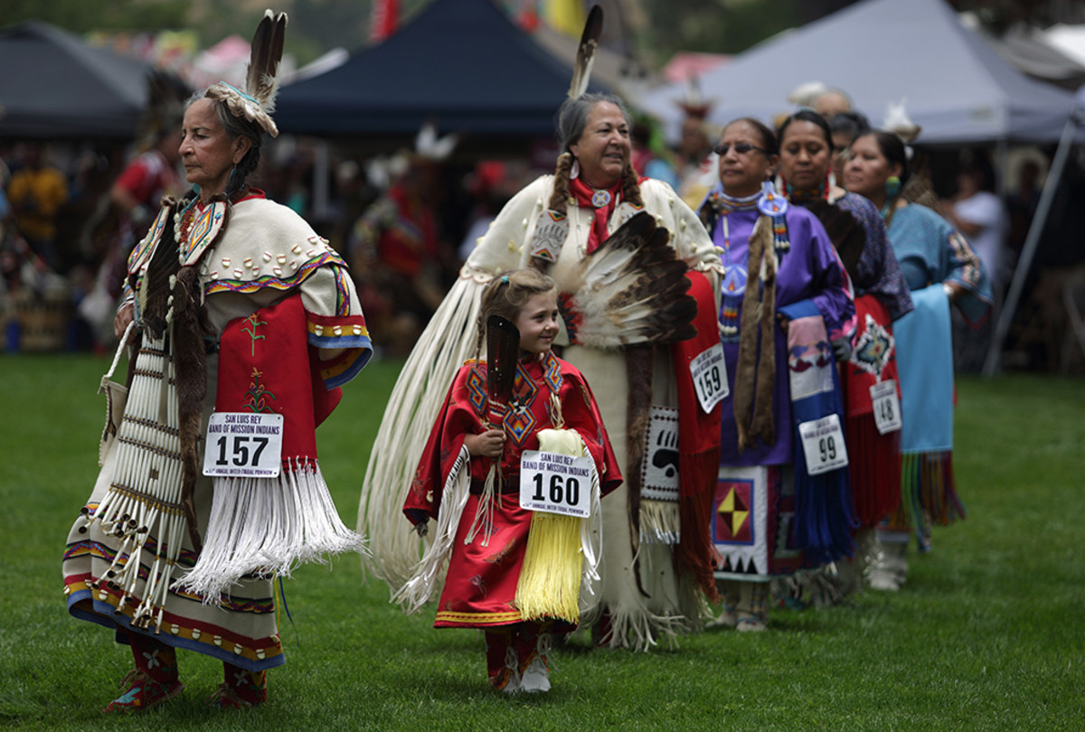 With one small and notable exception, female golden-age dancers make their way into the pow wow circle during grand entry in Oceanside, Calif. Diego James Robles