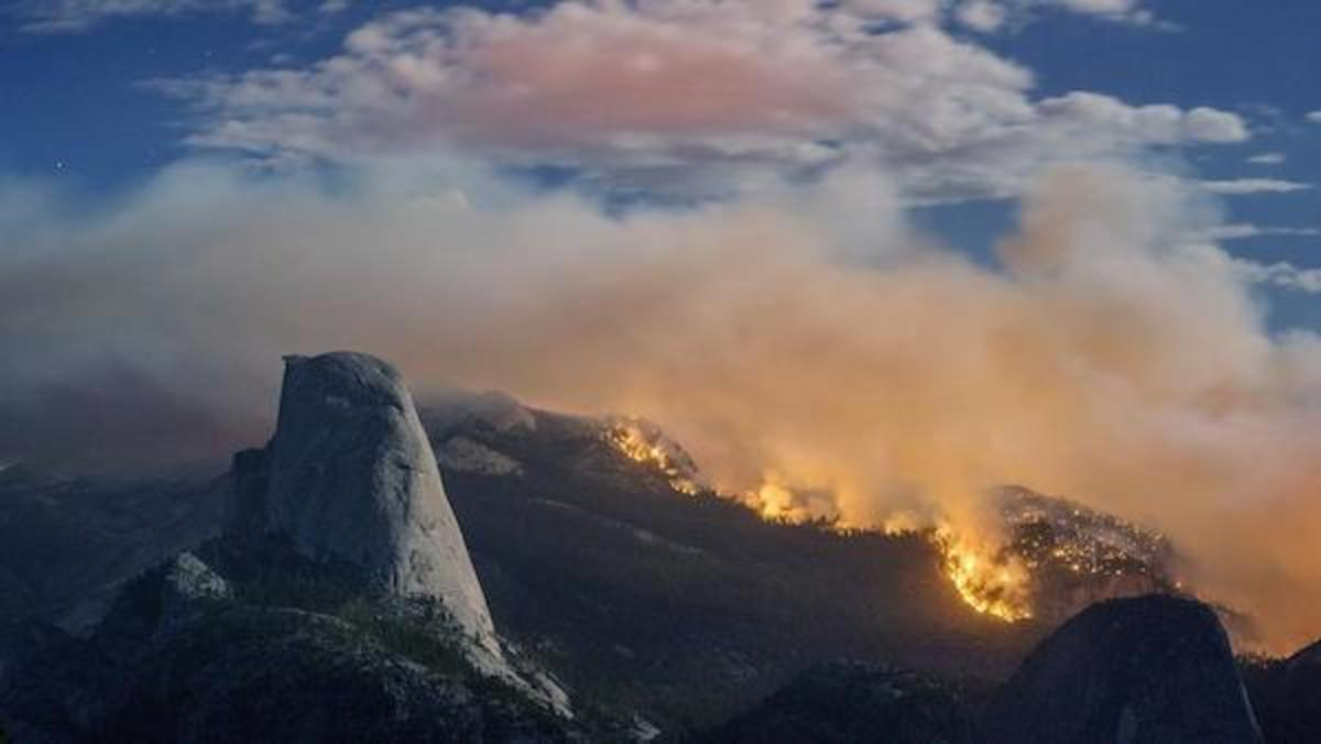 A wildfire burns next to Half Dome in Yosemite National Park.
