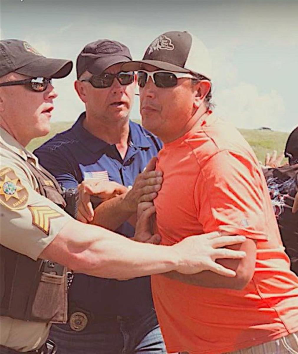 Standing Rock Sioux Tribe Chairman Chairman David Archambault II, in orange shirt, is arrested on August 12 for his part in blockading the Dakota Access oil pipeline construction site.
