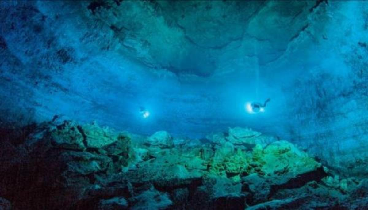 """Divers use lights to illuminate Hoyo Negro, an underwater cave in Mexico's Yucatan Peninsula where the remains of """"Naia,"""" a teenage girl who lived 12,000 to 13,000 years earlier, were found."""
