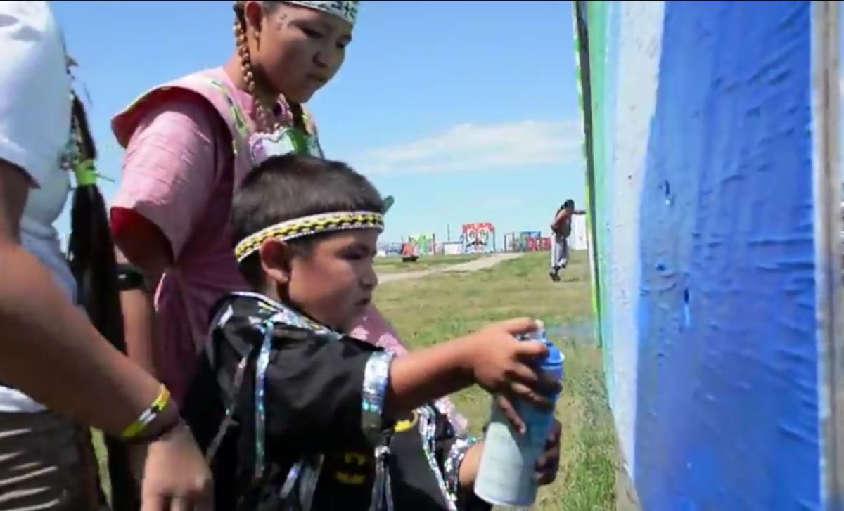 A young youth tests his painting skills at the RedCan Graffiti Jam. This year's event takes place June 29 to July 1 on the Cheyenne River Lakota reservation Eagle Butte community.