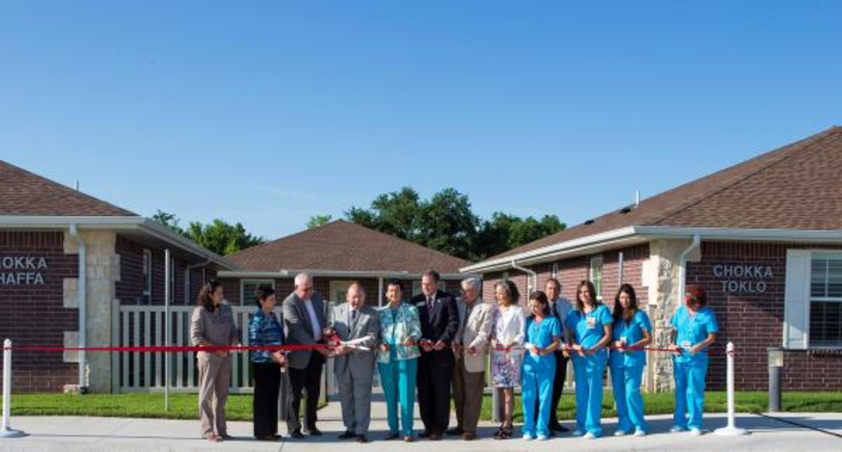 Chickasaw Nation Gov. Bill Anoatubby, center, is joined by tribal leaders and staff in a ribbon cutting ceremony for the new Chickasaw Nation Chikasha House. (Mike McKee)