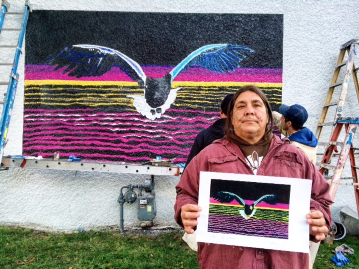 """Leonard Peltier's son Chauncey displays a print of his father's painting, """"On a Hunt,"""" while standing in front of a mural based on it, co-painted by Forrest Wozniak and Elijah Benson. It appears on the exterior of the White Page Gallery in Minneapolis, Minnesota, one of three Peltier murals in Minneapolis designed and supervised by artist Ira Coyne."""