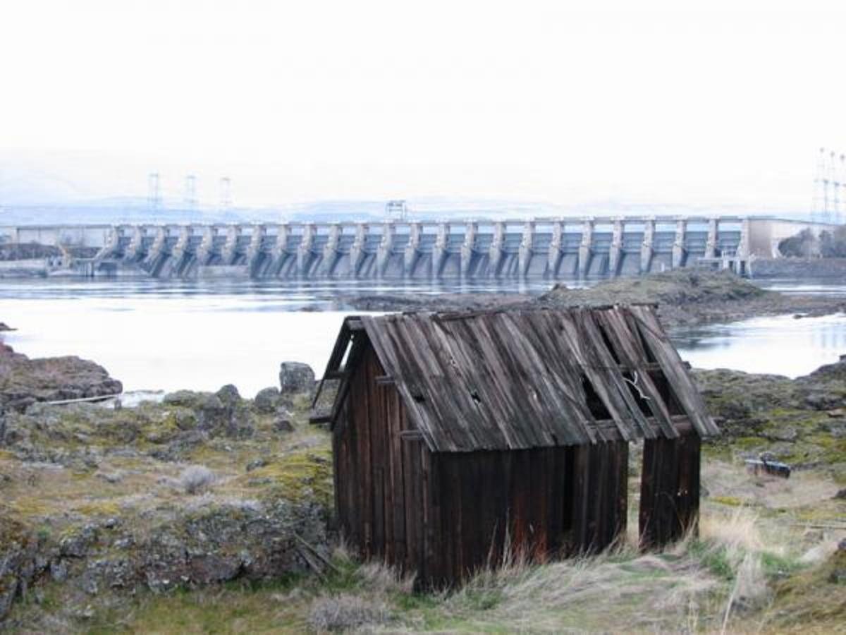 "An outbuilding of the historic Gulick Homestead in The Dalles, Oregon, United States, with the Columbia River and The Dalles Dam behind. The homestead is listed on the US National Register of Historic Places (NRHP) under the name ""Indian Shaker Church and Gulick Homestead""."